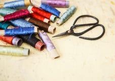 Ciseaux avec les fils en soie pour broder sur le fond de vintage Image stock