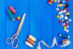 Ciseaux, bande de mesure, boutons, bobines des fils sur lumineux Images stock