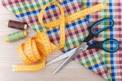 Ciseaux, bande-line, fils et tissu sur la table en bois Images stock