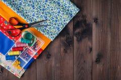 Ciseaux, bobines avec le fil et aiguilles, tissu rayé Photo stock