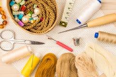 Ciseaux, boutons, fil, bande de mesure et approvisionnements de couture sur le fond en bois de lumière de tissu la vue du Images libres de droits