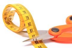Ciseaux coupant le ruban métrique sur le fond blanc Photographie stock libre de droits