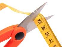 Ciseaux coupant le ruban métrique sur le fond blanc Photo stock