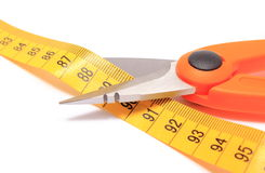 Ciseaux coupant le ruban métrique sur le fond blanc Image stock