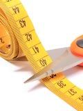 Ciseaux coupant le ruban métrique sur le fond blanc Photos libres de droits