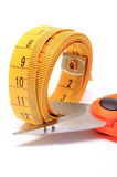 Ciseaux coupant le ruban métrique sur le fond blanc Photographie stock