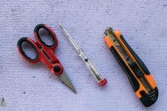 Ciseaux, coupeur et tournevis sur une table Outils d'un electri Image stock