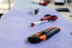 Ciseaux, coupeur et tournevis sur une table Outils d'un electri Photographie stock