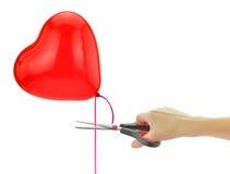 Ciseaux environ pour placer le ballon gratuit de coeur Image libre de droits
