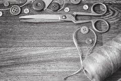 Ciseaux et boutons sur un blanc en bois de noir de fond Images libres de droits