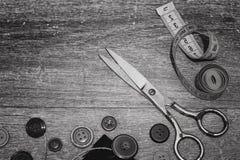 Ciseaux et boutons sur un blanc en bois de noir de fond Photos stock