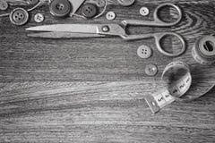 Ciseaux et boutons sur un blanc en bois de noir de fond Photographie stock libre de droits