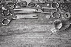 Ciseaux et boutons sur un blanc en bois de noir de fond Photo stock