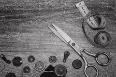 Ciseaux et boutons sur un blanc en bois de noir de fond Images stock