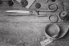 Ciseaux et boutons sur un blanc en bois de noir de fond Photos libres de droits