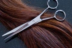 Ciseaux et cheveu de coiffeur Photographie stock libre de droits
