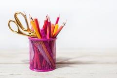 Ciseaux et crayons colorés de rouge-rose jaune et orange violets dans la tasse stationnaire sur la table en bois et le fond blanc Photos stock