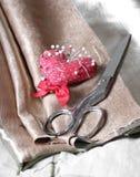 Ciseaux et goupille en métal sur le tissu brun Images stock