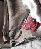 Ciseaux et goupille en métal sur le tissu brun Photo libre de droits
