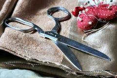 Ciseaux et goupille en métal sur le tissu brun Photographie stock