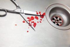 Ciseaux et sang dans l'évier Images stock