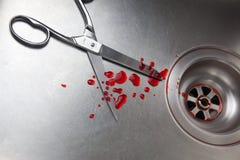 Ciseaux et sang dans l'évier Photo stock