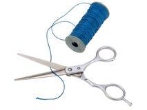 Ciseaux et une bobine de fil bleu sur le fond blanc Photographie stock libre de droits