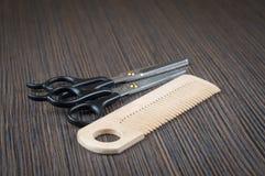 Ciseaux et une brosse à cheveux sur un dessus de table en bois foncé photos libres de droits