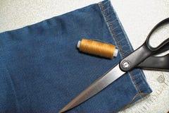 Ciseaux, fil, et jeans sur le bureau photo libre de droits