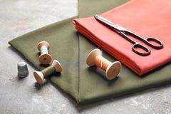 Ciseaux, fils et tissu sur la table grise Régler le matériel Photos libres de droits