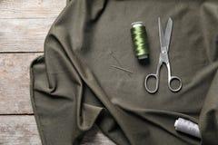 Ciseaux, fils et tissu sur le fond en bois, Image stock