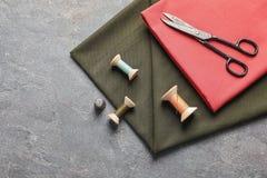 Ciseaux, fils et tissu sur le fond gris Images stock