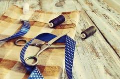 Ciseaux, fils, tissu et bande bleue Images stock