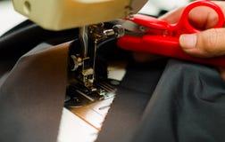 Ciseaux rouges aidant un procédé de fabrication de robe, machine à coudre sur le tissu bleu Photo stock