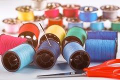 Ciseaux rouges, aiguille et diverses bobines de fil sur le fond blanc toned Images stock