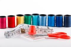 Ciseaux rouges, bande de mesure et dé avec des bobines de fil sur le fond blanc Photo libre de droits