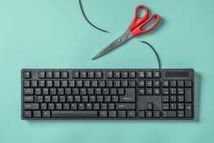 Ciseaux rouges et un clavier avec un fil coupé Idée et concept pour le sujet de la censure ou de la liberté de la presse images libres de droits