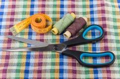 Ciseaux vestimentaires, bande-line, fils et aiguilles sur le tissu Photographie stock