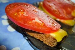 Ściska z czarnymi chleba, serowych i soczystych pomidorami, Obrazy Royalty Free