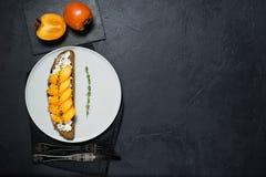 ?ciska z persimmon i mi?kkim serem na czarnym tle z przestrzeni? dla teksta zdjęcia stock
