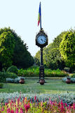 Cismigiu Park, Bucharest, Romania. Flowerbeds, clock and Romanian flag at start of main grass passage in Cismigiu Park, Bucharest, Romania royalty free stock images