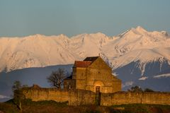 Medieval fortress in Transylvania with the Carpathians in the background. Cisnadioara medieval fortress in Transylvania with the snowy Transylvanian Alps in the Stock Photo