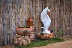Cisne plástica branca decorativa em uma cerca de bambu Foto de Stock