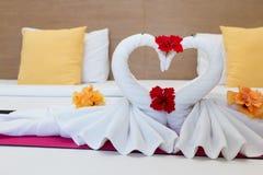 Cisnes blancos hechos de las toallas en cama Foto de archivo libre de regalías