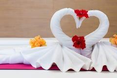 Cisnes brancas feitas das toalhas na cama Imagem de Stock