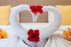 Cisnes brancas feitas das toalhas na cama Imagens de Stock Royalty Free