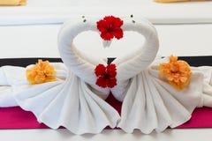 Cisnes brancas feitas das toalhas na cama Imagem de Stock Royalty Free