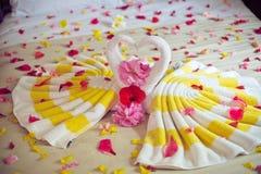 Cisnes de la toalla del blanco dos y rosa del rojo en la cama en traje de la luna de la miel Fotografía de archivo