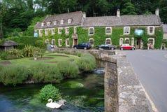 Cisnes en el río Coln delante del hotel del cisne, Bibury, Inglaterra fotos de archivo libres de regalías