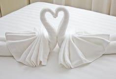 Cisnes feitas das toalhas na cama Fotografia de Stock Royalty Free